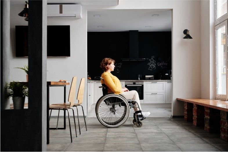 paralyzed woman in a wheelchair staring out the window